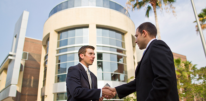 Two businesspeople shaking hands with the college in the background.